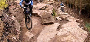 a golspie mountain biking cyclist, riding over rocks